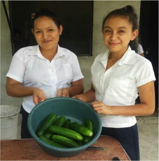 Students show the cucumbres grown in the school garden, established under the joint programme