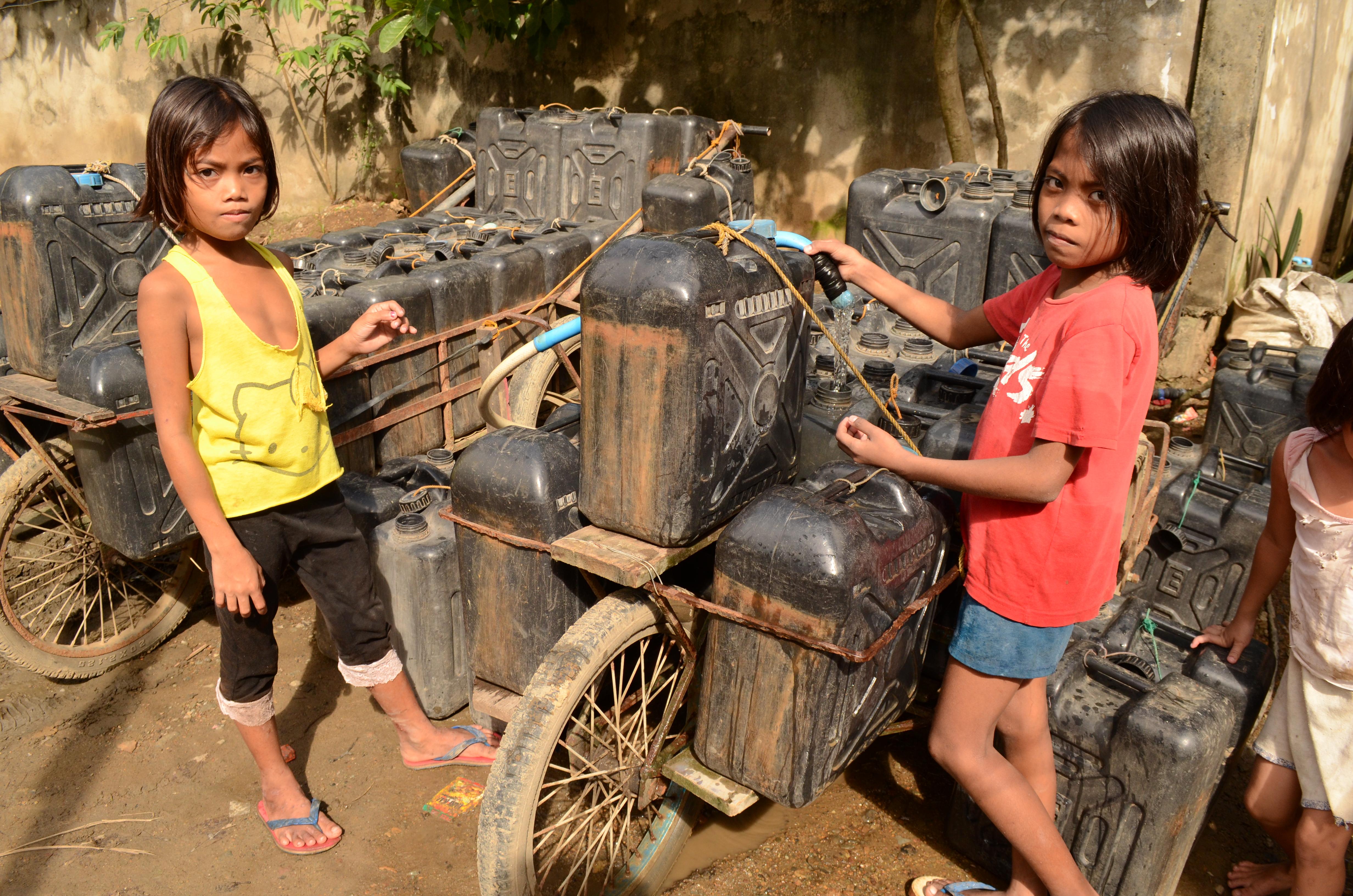 """Niñas de una municipalidad """"sin agua"""" ayudan a cargar una carreta con bidones de agua para llevarlos a sus casa"""