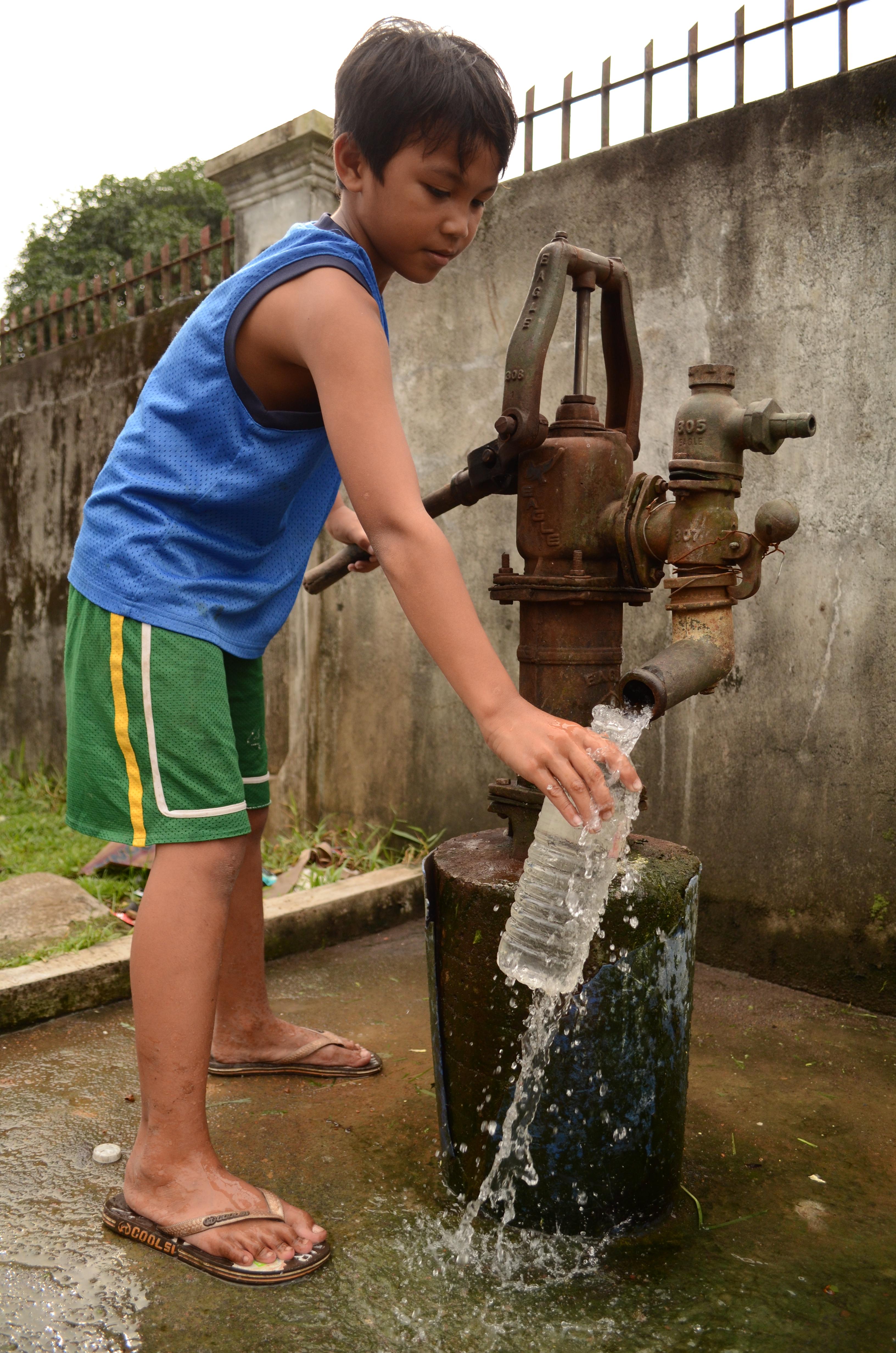 Un niño rellena su botella de agua
