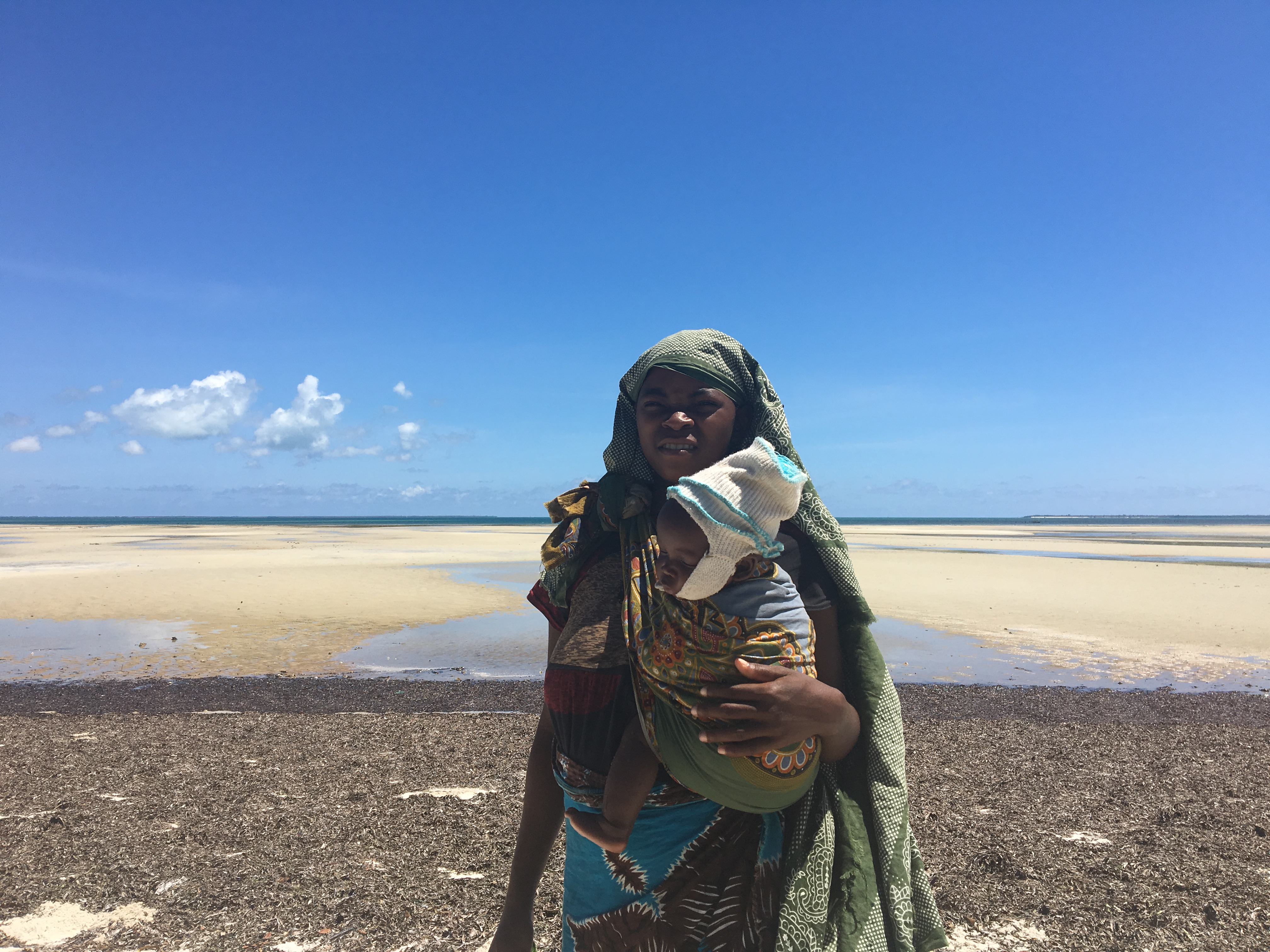 A programme beneficiary, behind her, the site of offshore gas field and platform now under construction, in Palma, Cabo Delgado.