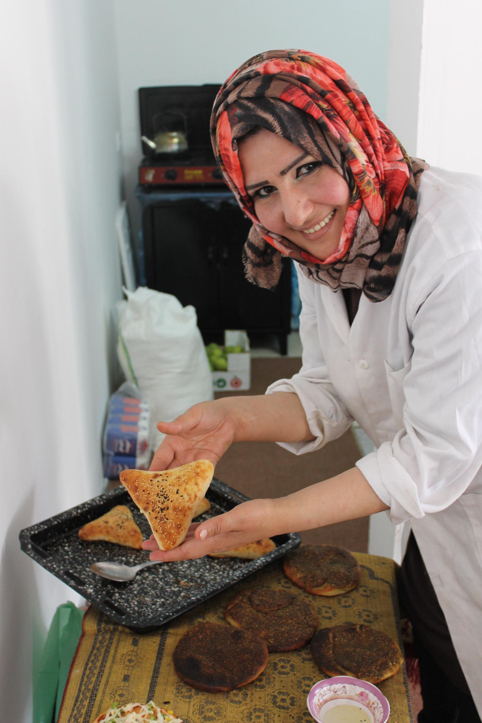 A woman prepares traditional, savoury baked goods called Mu' ajanat in the Halhoul Business shop